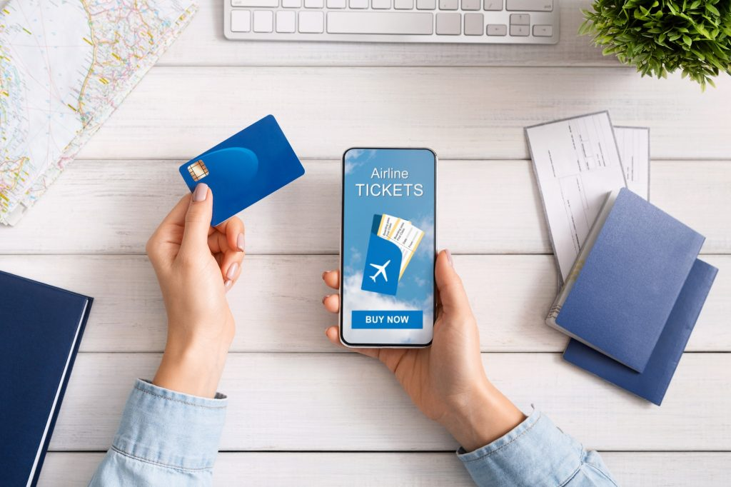 Woman holding credit card and smartphone buying plane tickets online
